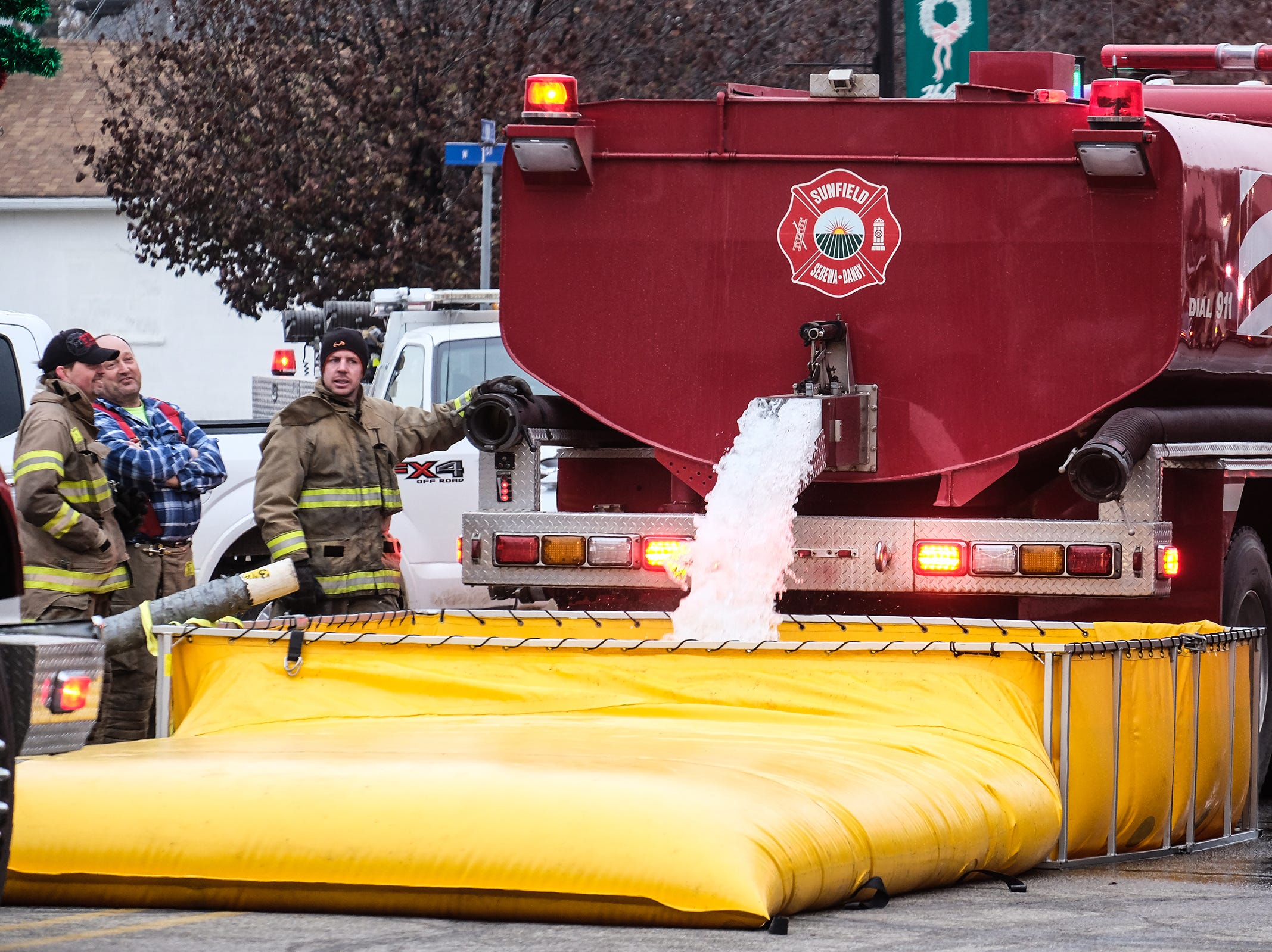 Tanker trucks fill water containers in Fowler to use against a fire that destoyed buildings in the downtown area Saturday, Dec. 15, 2018.