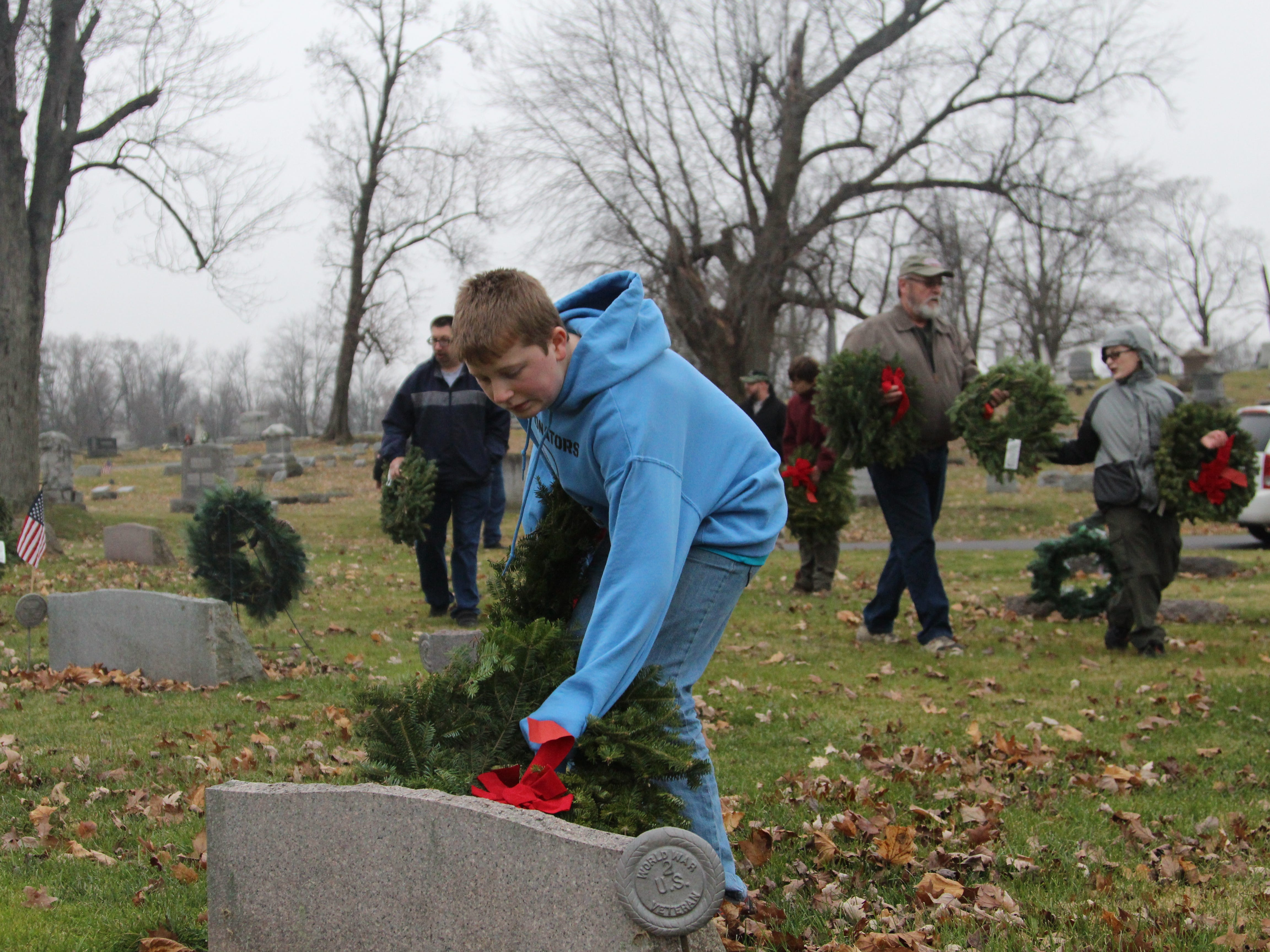 Aaron French, 12, places a wreath on the grave of a World War II veteran at Marion Cemetery. He was among the volunteers to place the donated wreaths in honor of veterans Saturday during Wreaths Across America, a nationwide effort to honor veterans during the holiday season.