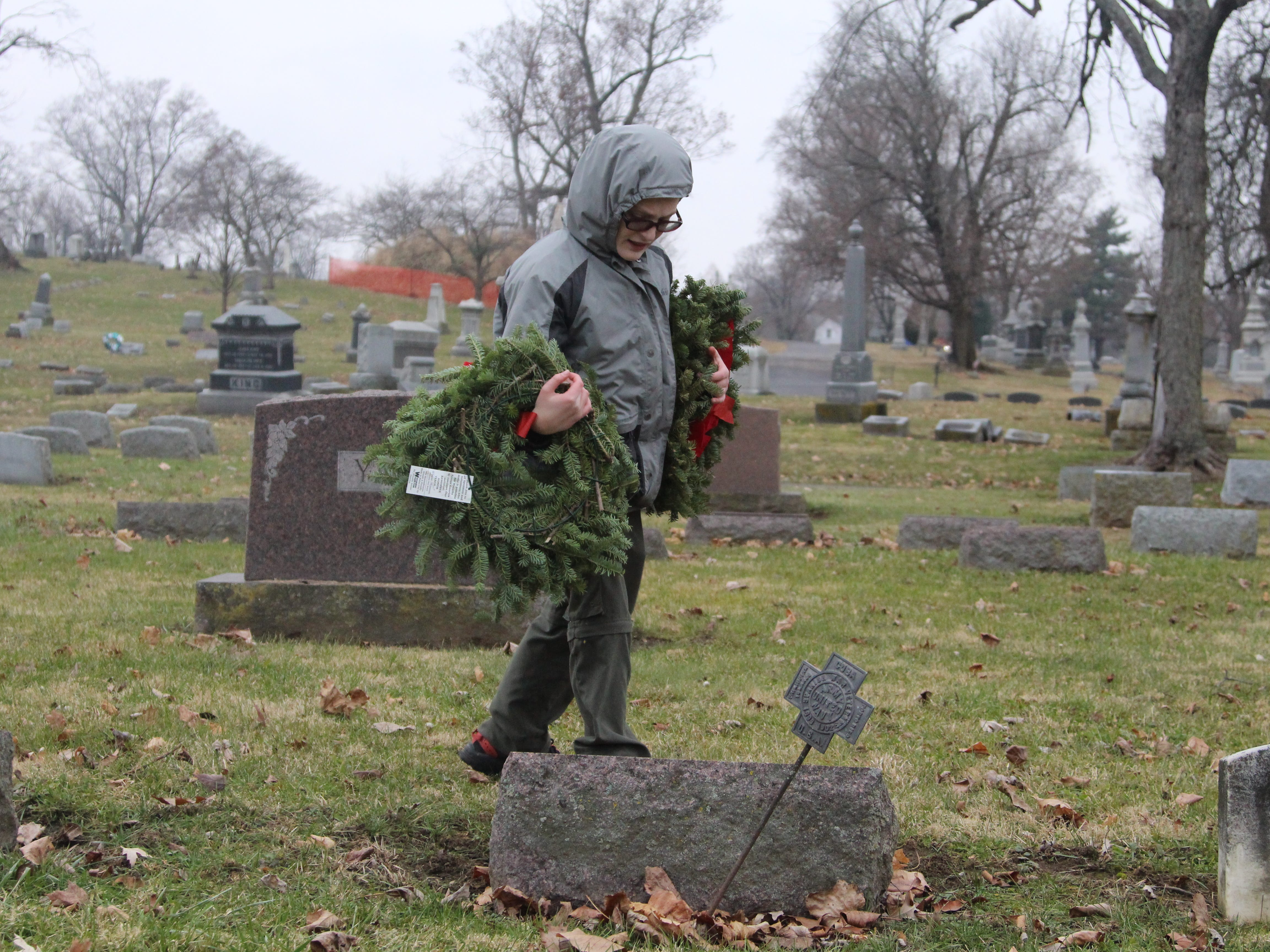 Zach Wolfe, 11, places wreaths on the graves of local veterans Saturday at Marion Cemetery as part of Wreaths Across America, a nationwide effort to honor veterans during the holiday season. Wolfe is a boy scout in Troop 46 in Marion.