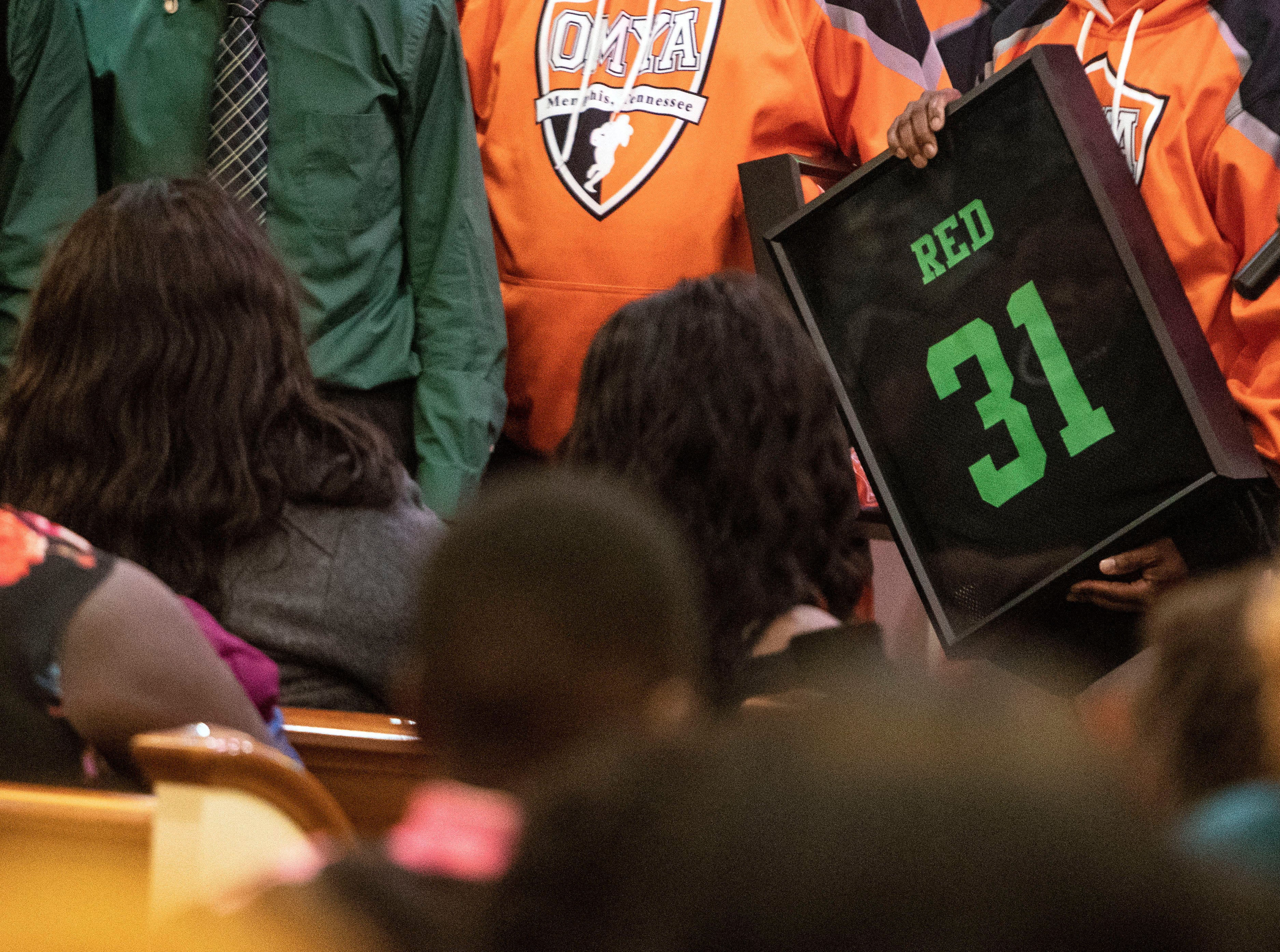 Kameren Johnson's parents are presented with a green and black jersey with Kameren's name and number, from the Orange Mound Youth Association, during the funeral, Saturday, Dec. 15, 2018.
