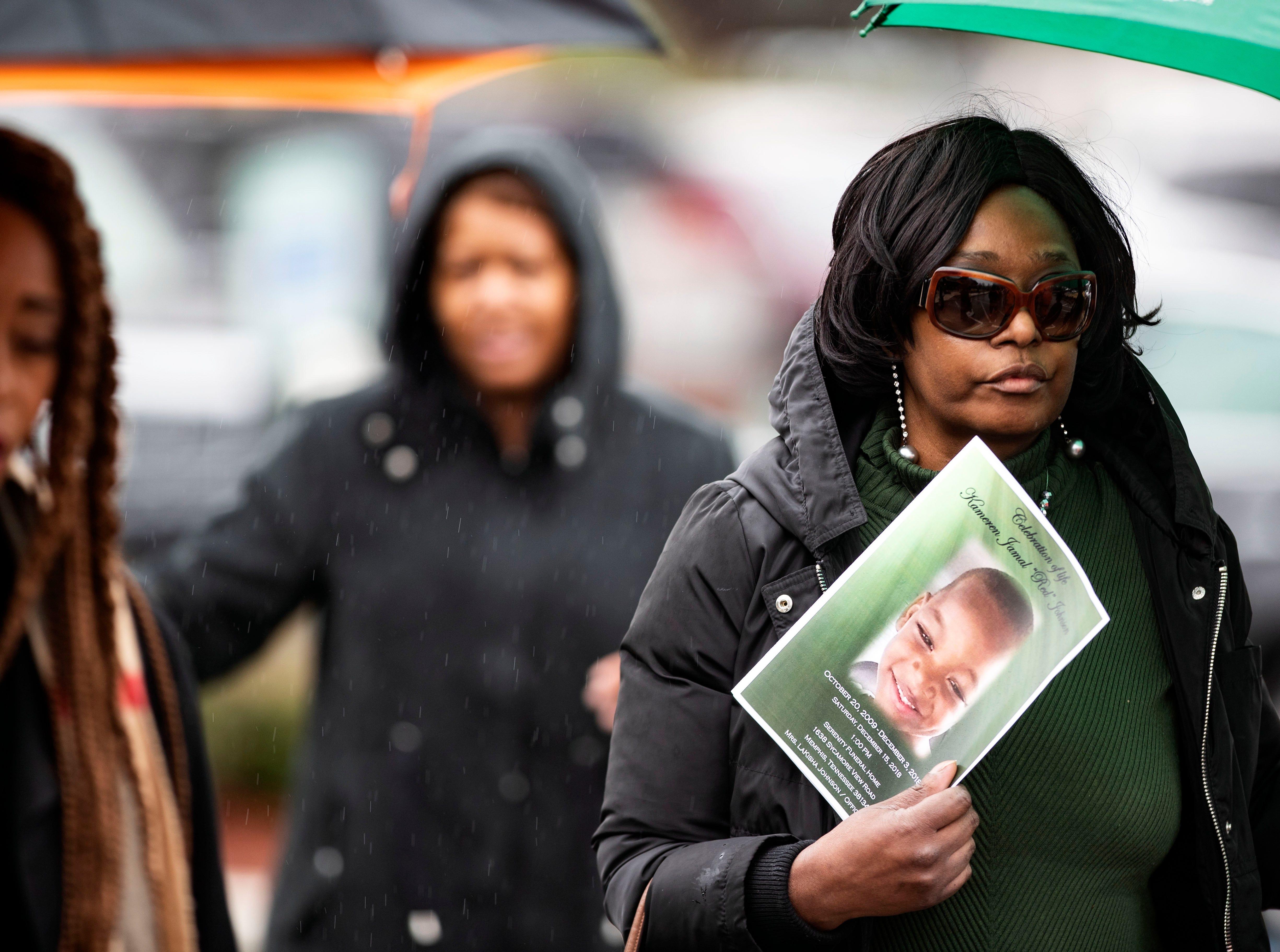 Attendants of 9-year-old Kameren Johnson's funeral, walk under umbrellas to burial site, Saturday, Dec. 15, 2018.