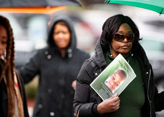 Attendants of 9-year-old Kameren Johnson's funeral walk under umbrellas to the burial site on Saturday.