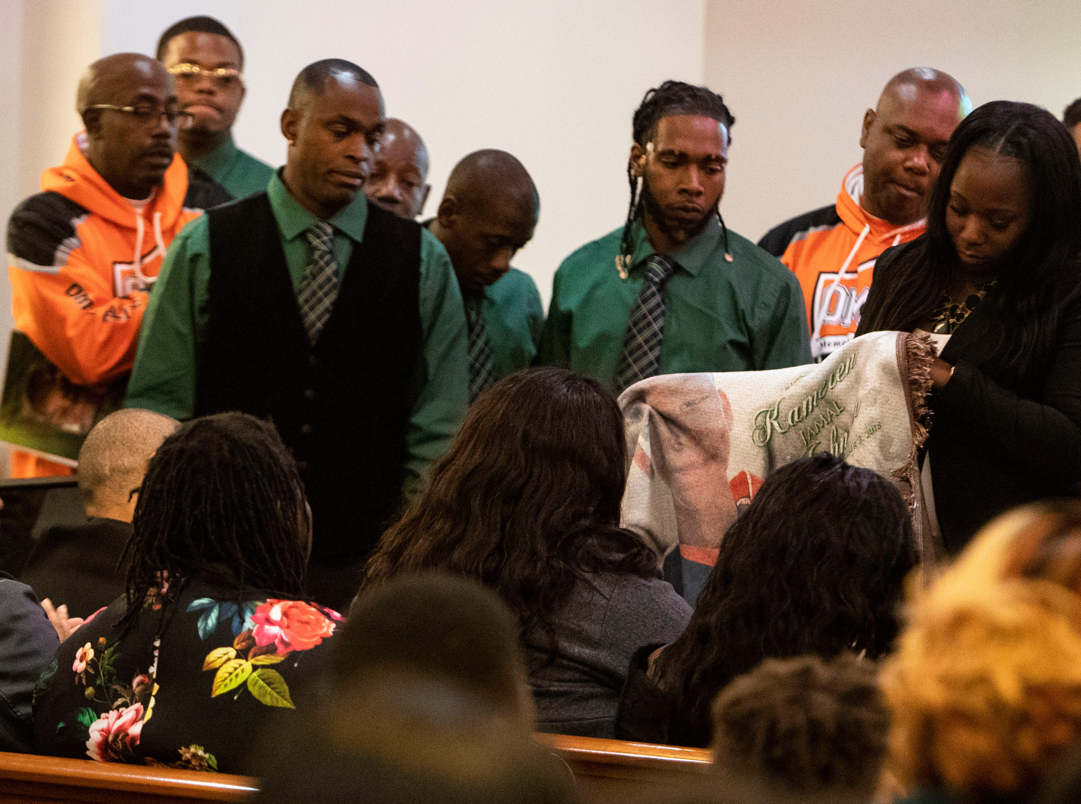 Kameren Johnson's parents are presented with a custom made blanket from the mothers of Orange Mound Youth Association, during the funeral, Saturday, Dec. 15, 2018.