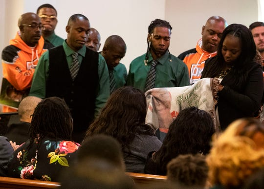 Kameren Johnson's parents are presented with a custom made blanket from mothers that are part of the Orange Mound Youth Association during Kameren's funeral Saturday.