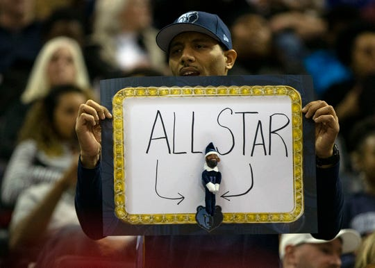 A Grizzlies fan holds up an All-Star poster for Mike Conley at FedExForum on Dec. 14.