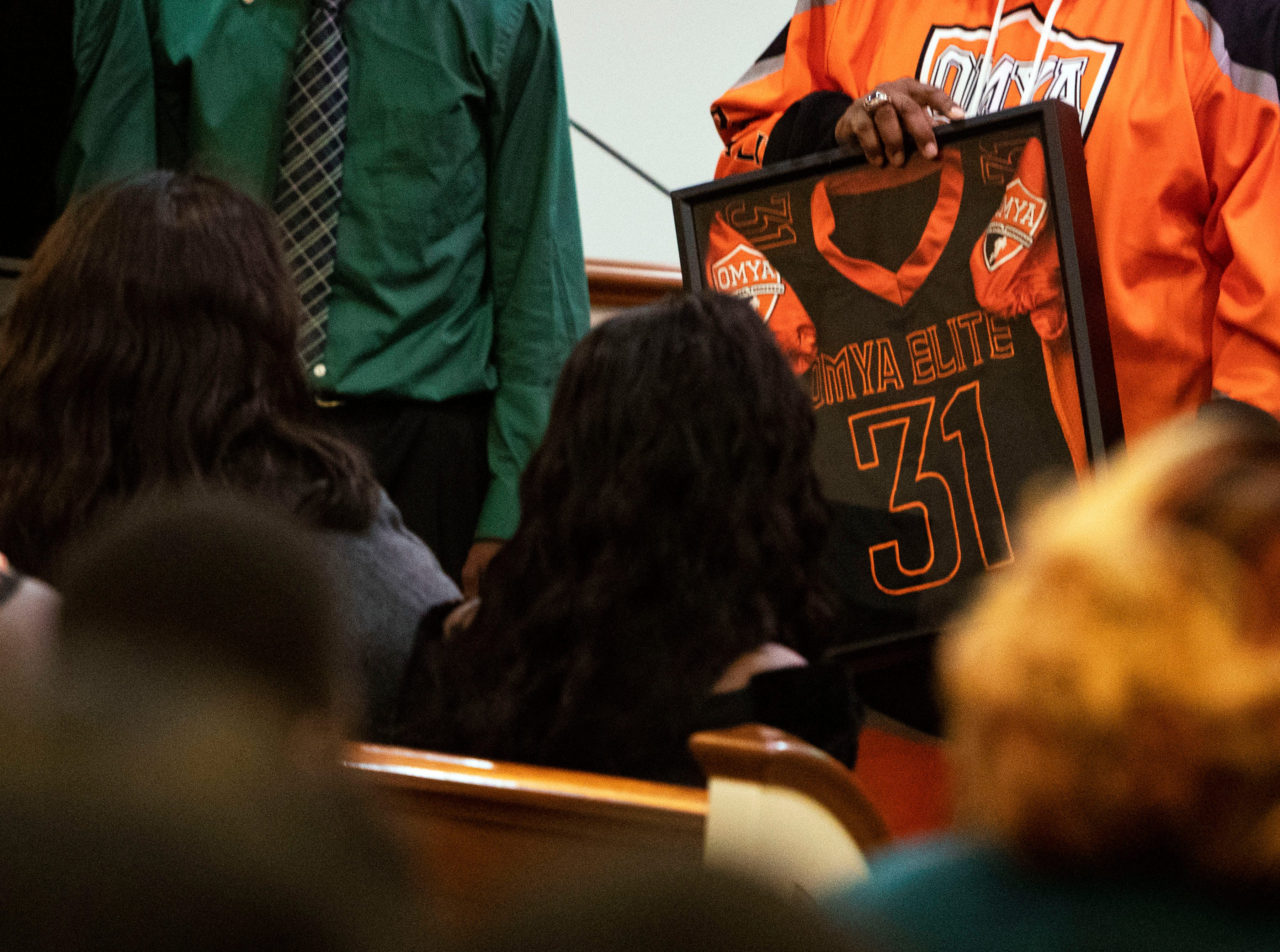 Kameren Johnson's parents are presented with jersey he wore before deadly bus crash, from the Orange Mound Youth Association, during the funeral, Saturday, Dec. 15, 2018.