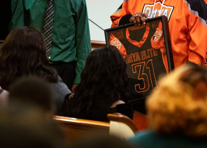 Kameren Johnson's parents are presented with jersey he wore before deadly bus crash, from the Orange Mound Youth Association, during Kameren's funeral on Saturday.