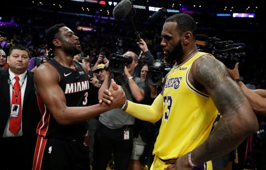 Miami Heat guard Dwyane Wade, left, shakes hands with Los Angeles Lakers' LeBron James at the end of an NBA basketball game on Dec. 10.