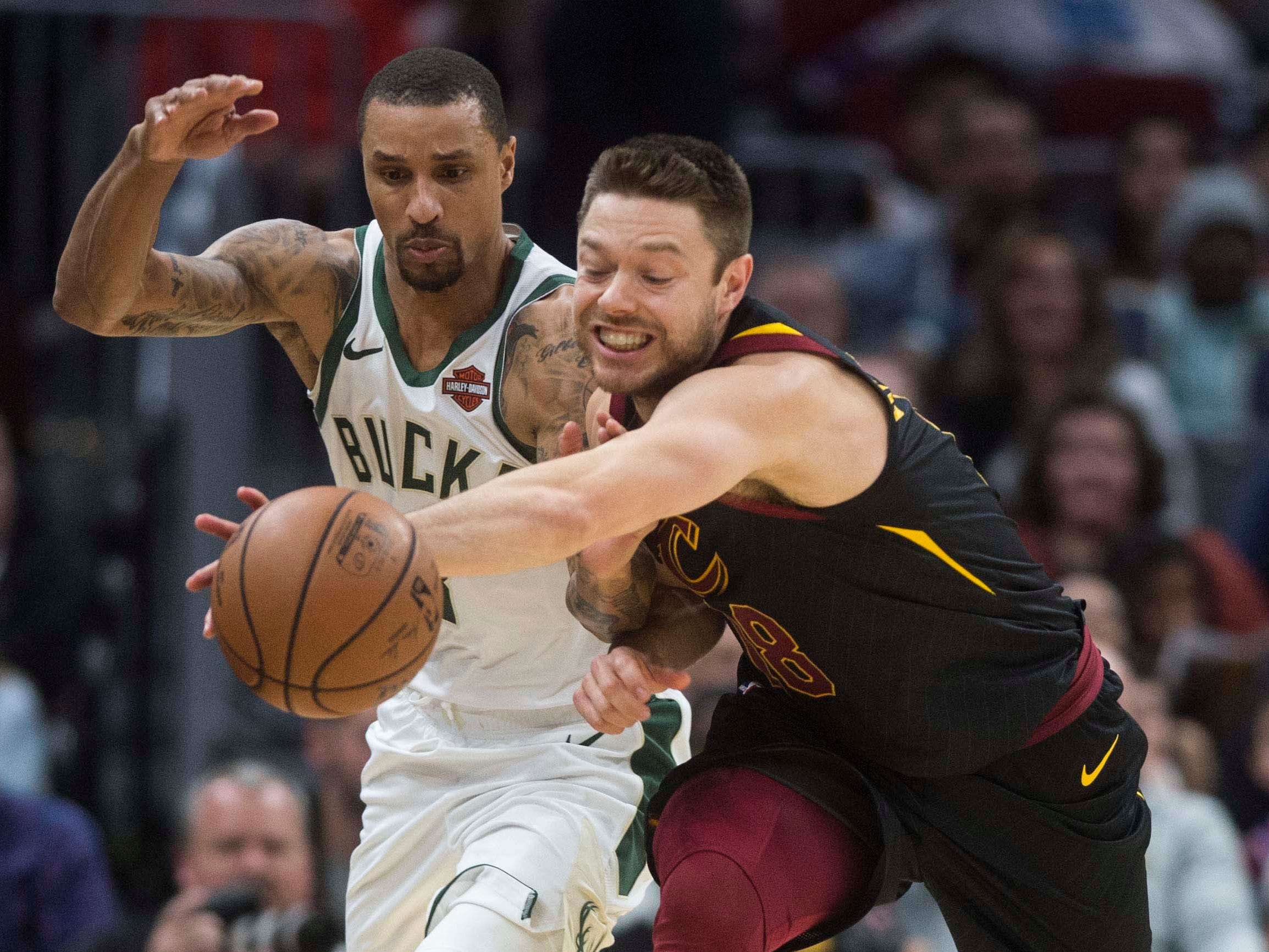 Bucks guard George Hill and Cleveland Cavaliers guard Matthew Dellavedova fight for a loose ball.
