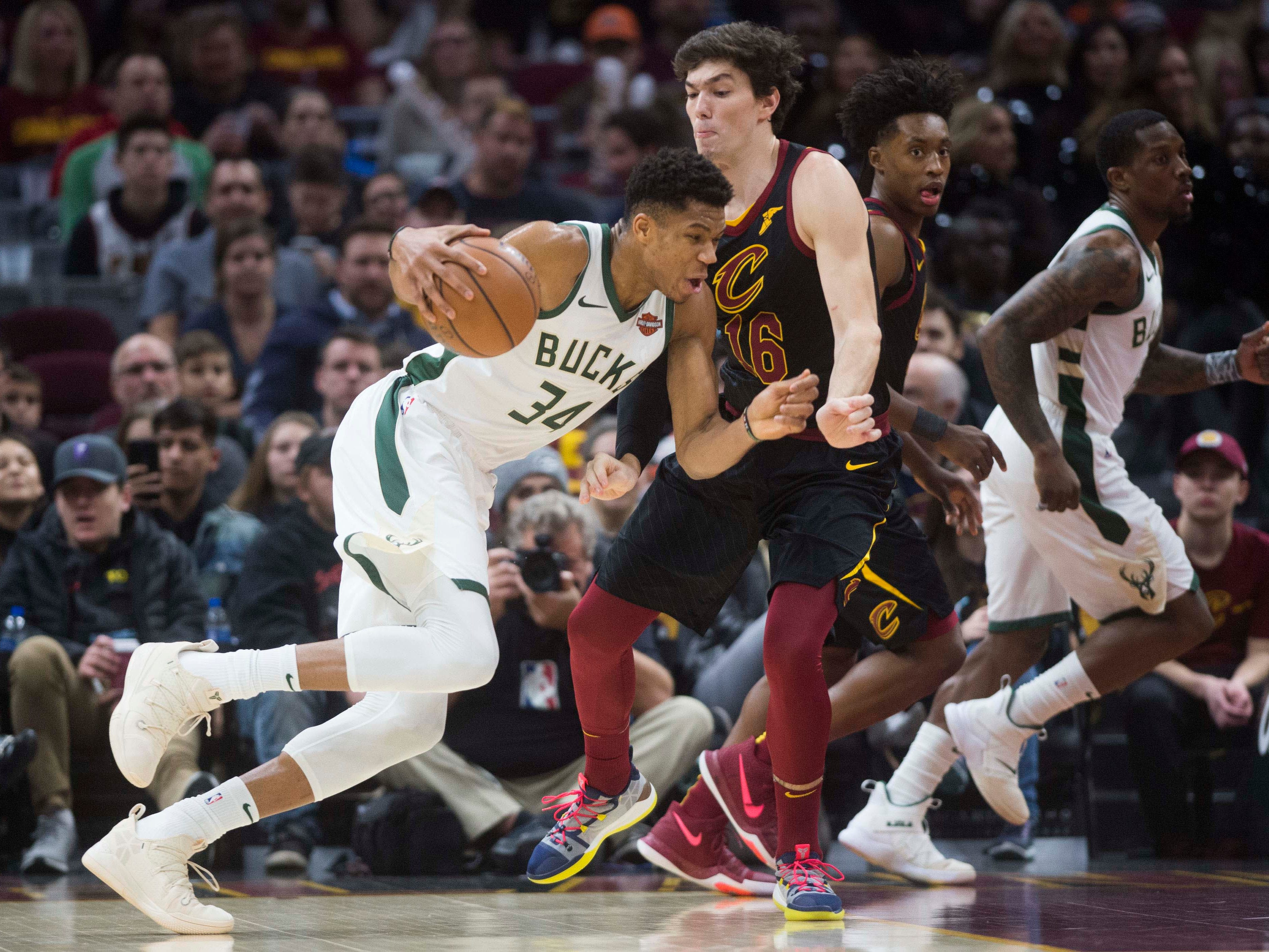 Bucks forward Giannis Antetokounmpo drives to the basket against Cleveland Cavaliers forward Cedi Osman.