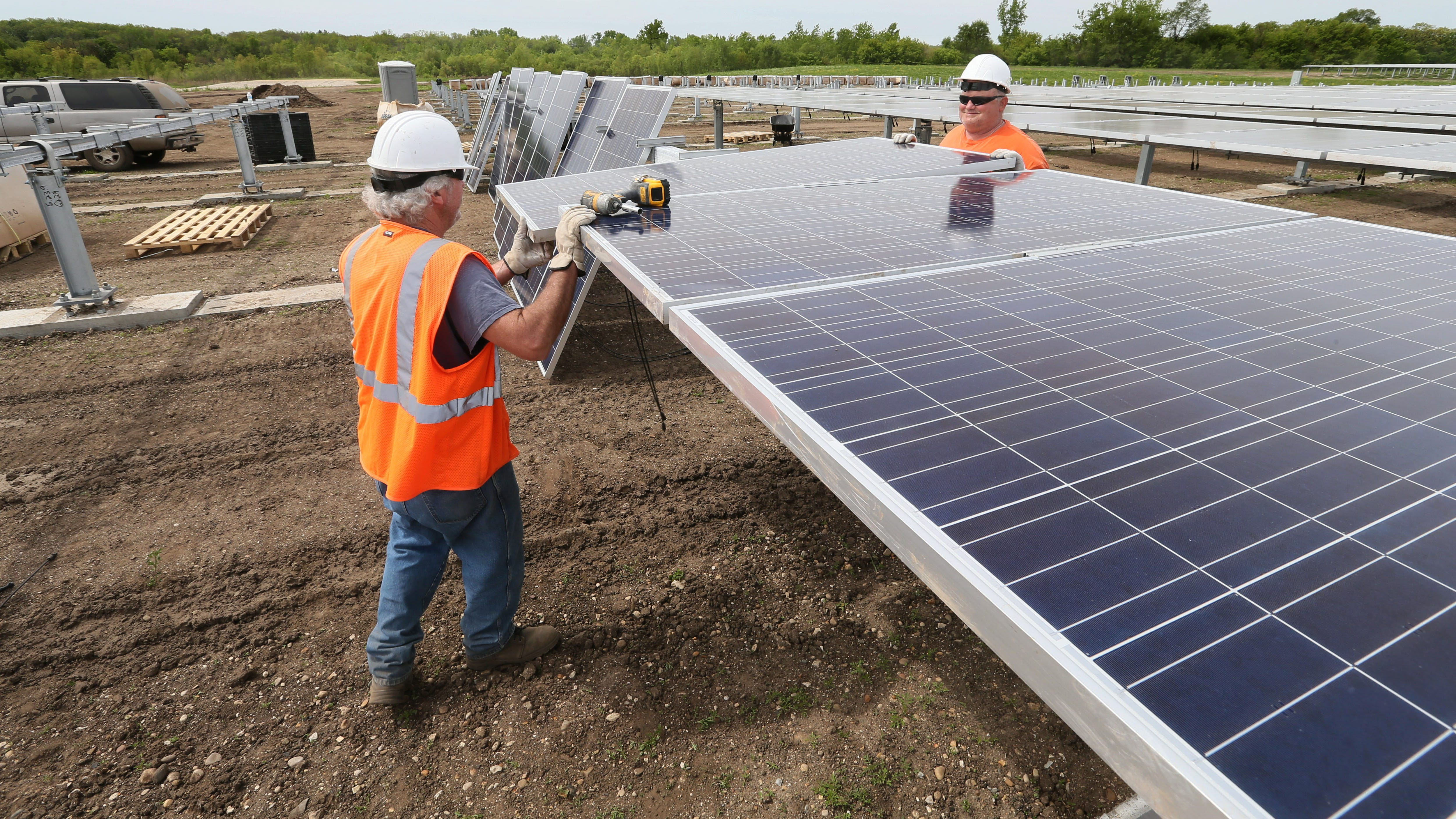 Left is Max Huntington (left) and Chris Podest instal solar panels in May on metal frames on top of an Alliant Energy coal-ash landfill at the Rock River generating station in Beloit.