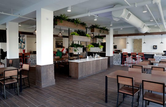 White walls, ceiling and pillars set off green plants in Crossroads Collective, which has a common seating area plus seats at a bar and at individual vendors, for 94 seats in all. The east side food hall's capacity is 161.