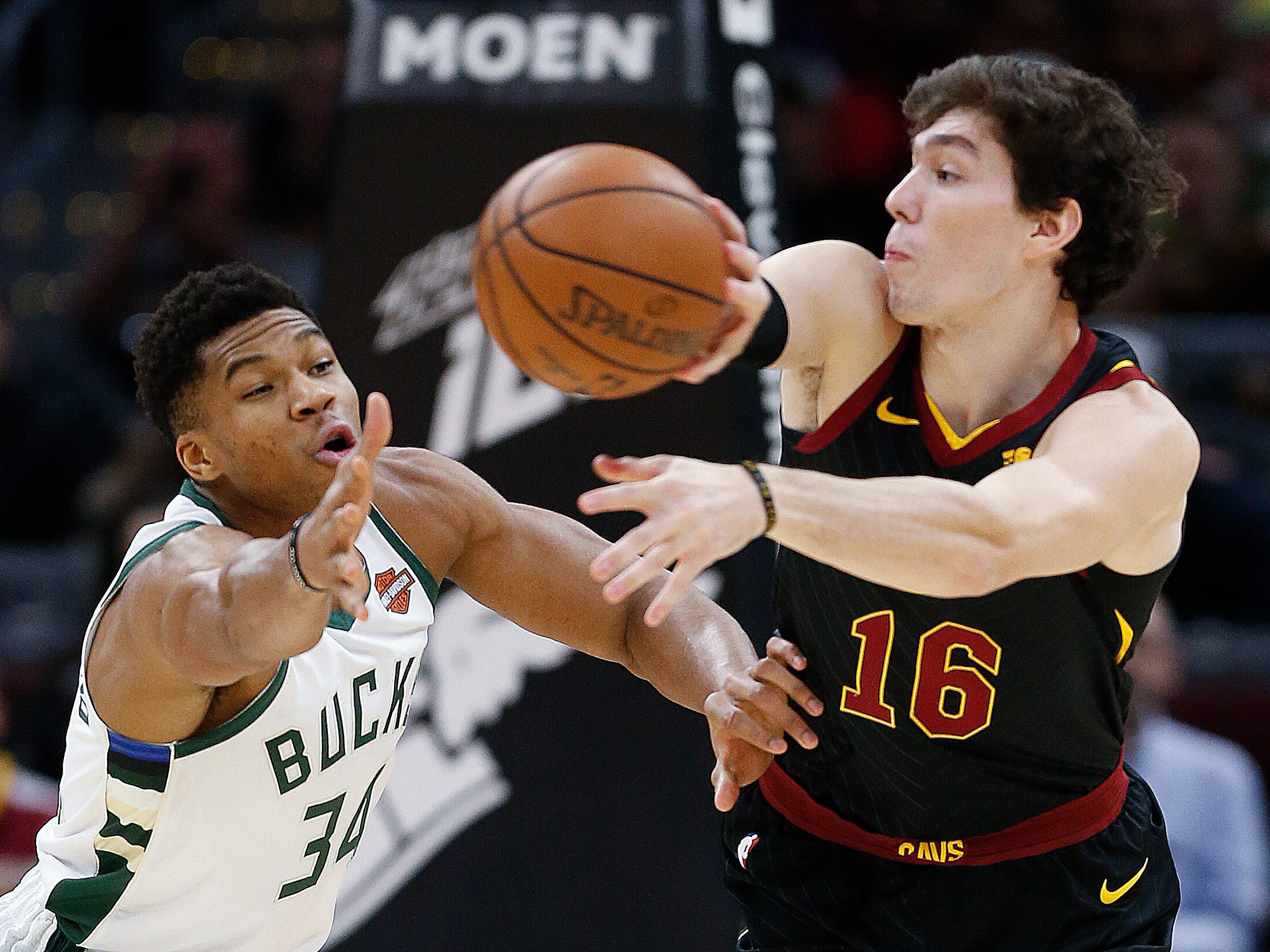 Cedi Osman tries to pass the ball around Giannis Antetokounmpo.
