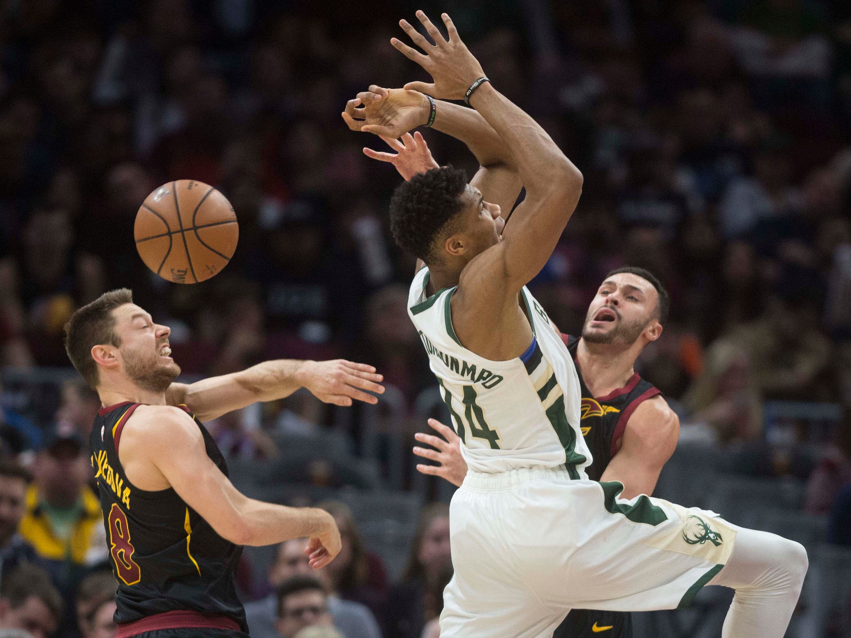 Bucks forward Giannis Antetokounmpo tries to drive between Cleveland Cavaliers guard Matthew Dellavedova and forward Larry Nance Jr.