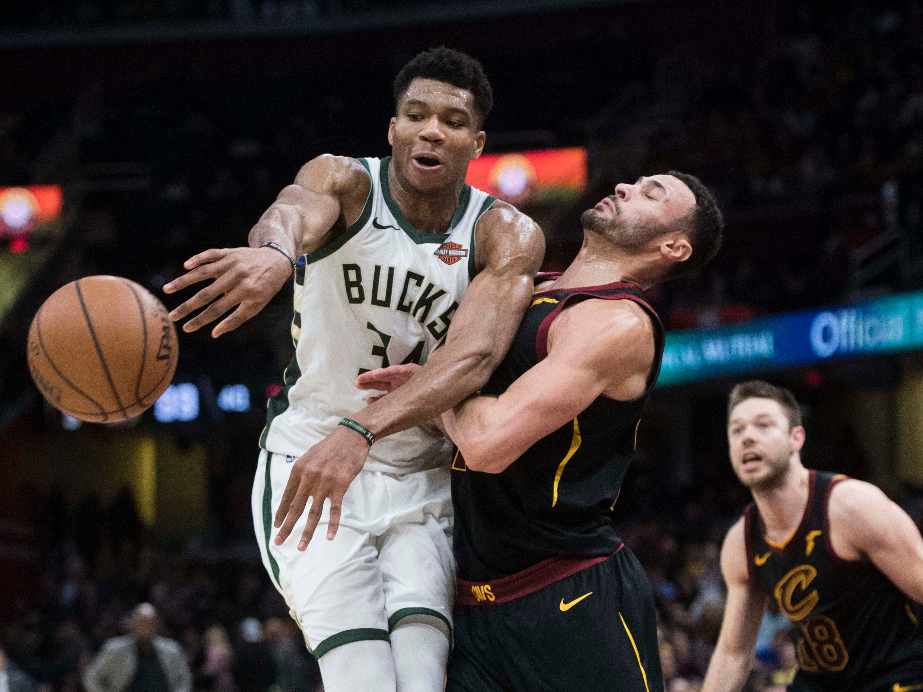 Bucks forward Giannis Antetokounmpo passes the ball as Cleveland Cavaliers forward Larry Nance Jr. defends.