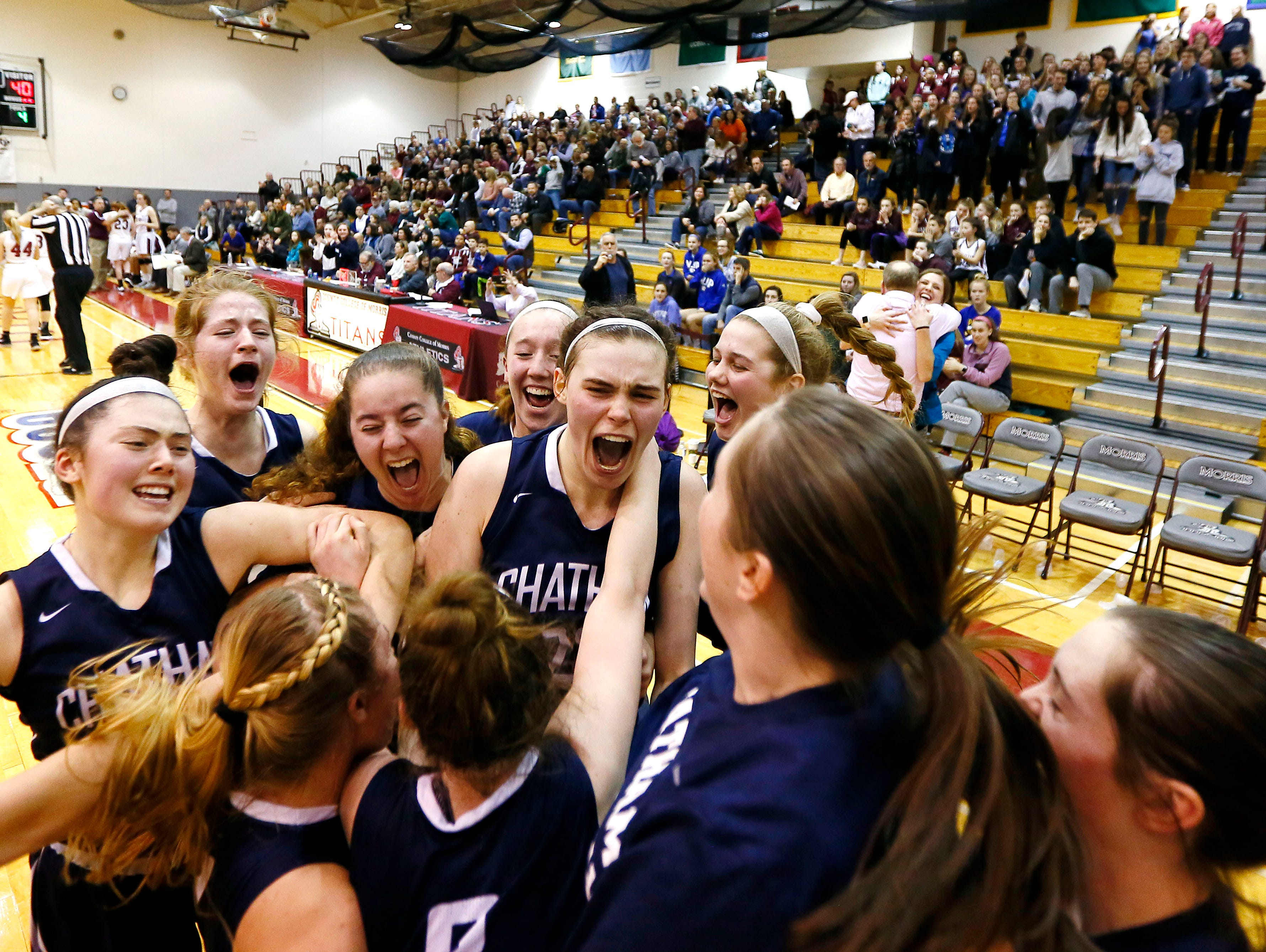 Chatham's Veronica Kelly, c,  celebrates with teammates after defeating Morristown during the 44th annual Morris County girls basketball tournament final at County College of Morris.  Chatham defeated Morristown, 40-31, to claim its first Morris County Tournament girls title. February 22, 2018. Randolph, NJ.