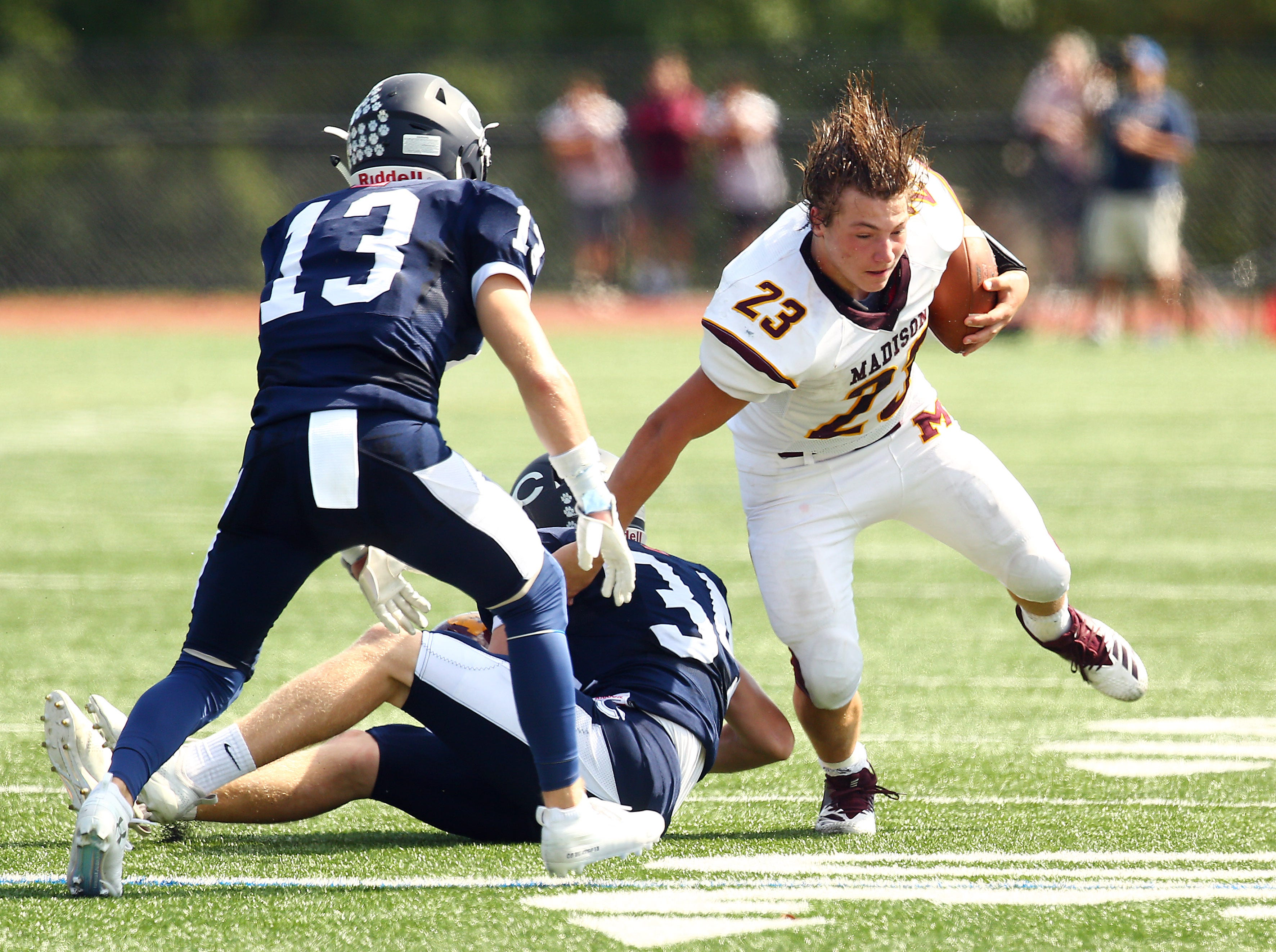 Madison running back Austin Schmitz breaks a tackle, losing his helmet to Chatham's James Ehler during their SFC American White Saturday football game. September 29, 2018, Chatham, NJ