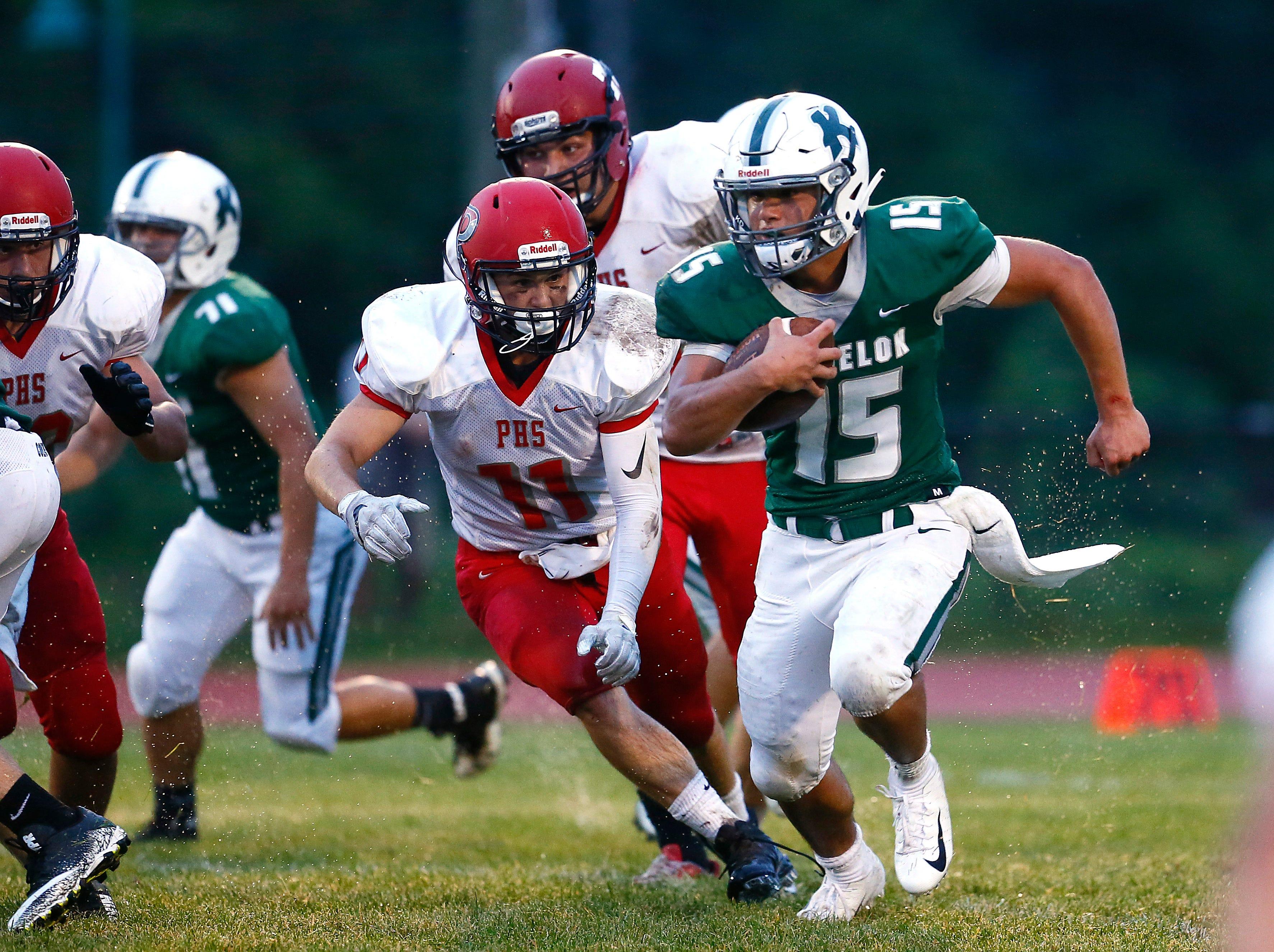 Kinnelon quarterback Joe Rymarz picks up a first down vs. Parsippany during their SFC American Blue football season opener. August 31, 2018, Kinnelon, NJ