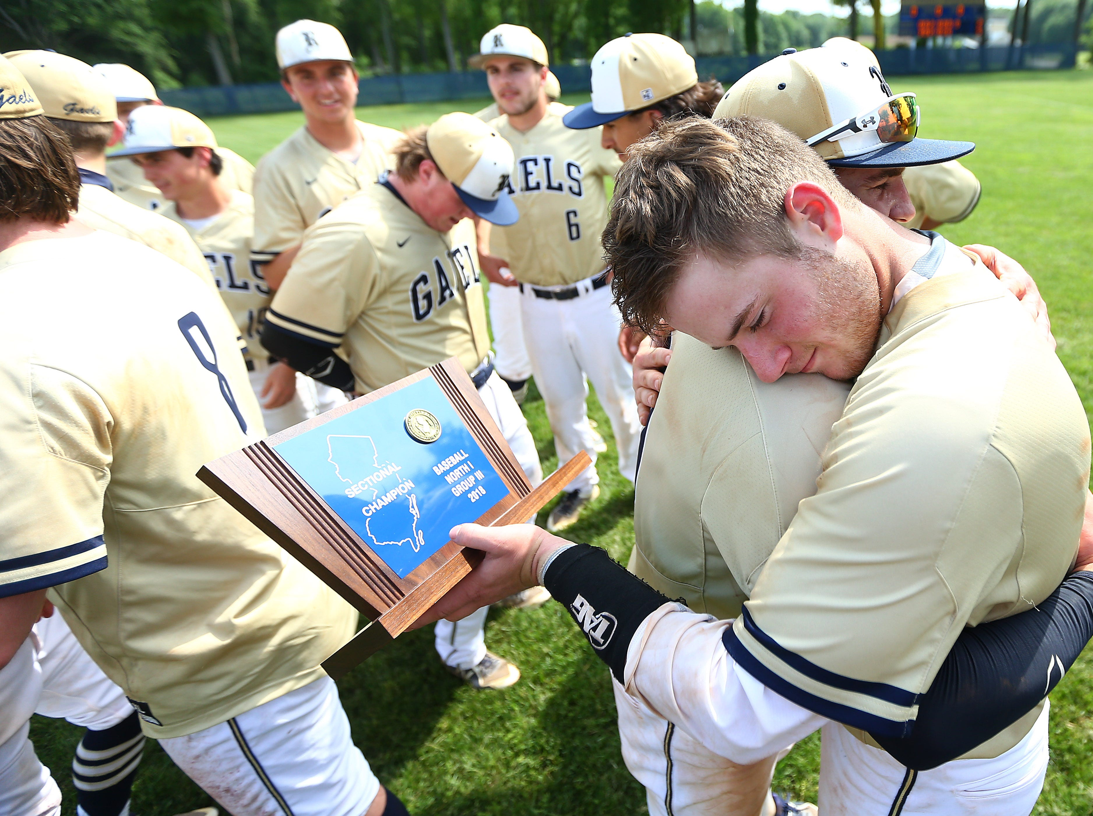 Roxbury's Michael Roumes and Andy Axelson hug with the champions trophy after defeating Pascack Valley in the NJSIAA North 1 Group III baseball final. June 1, 2018. Roxbury, NJ