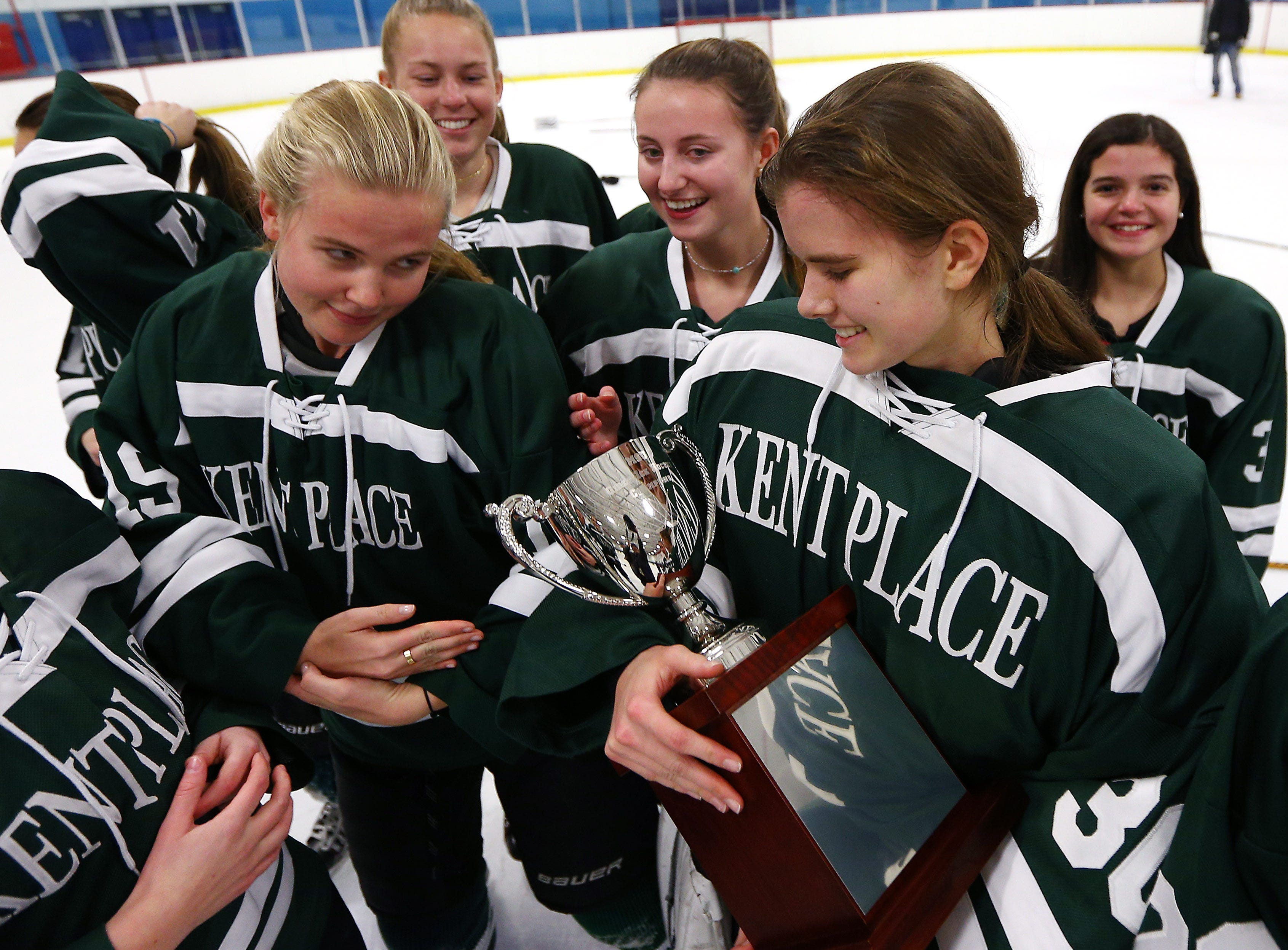 Kent Place goaltender Isla Okkinga gets a tip from teammate Natalie Gilfillan how to cradle the winning trophy after defeating Chatison in the inaugural MUGIHL Girls Ice Hockey League final at Mennen Arena. February 20, 2018. Morris Twp, NJ.