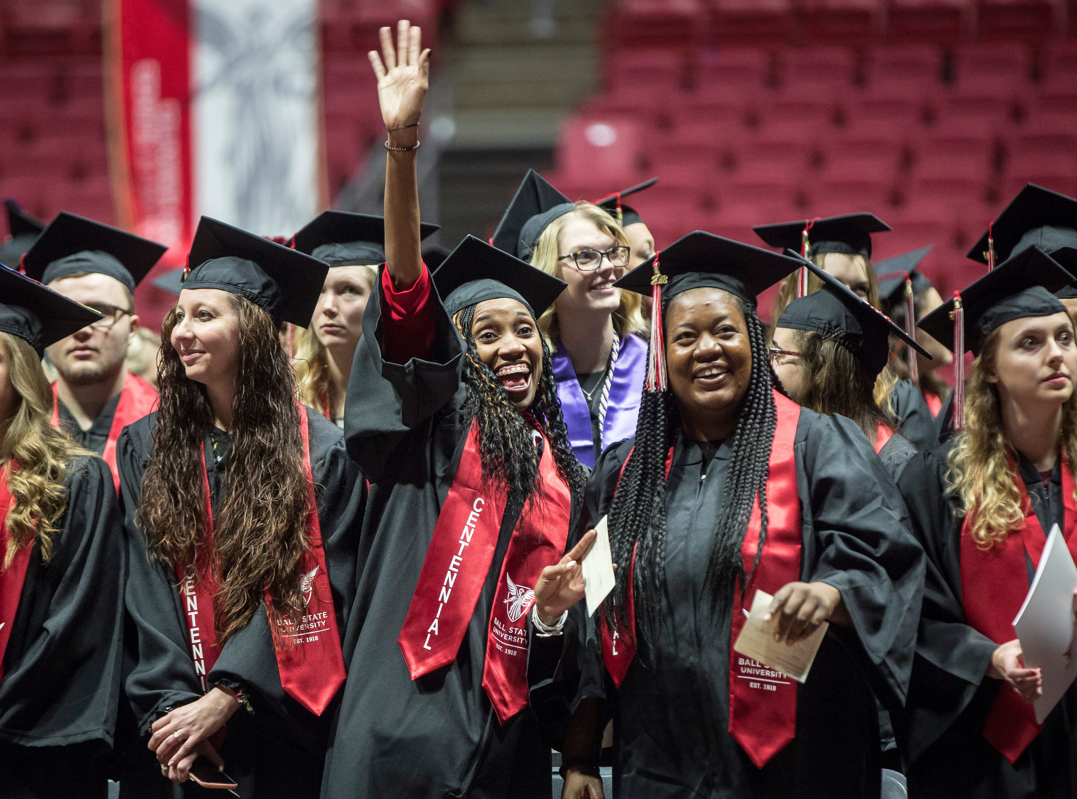 Students wave at family and friends during the 184th commencement ceremony on Saturday at Worthen Arena.