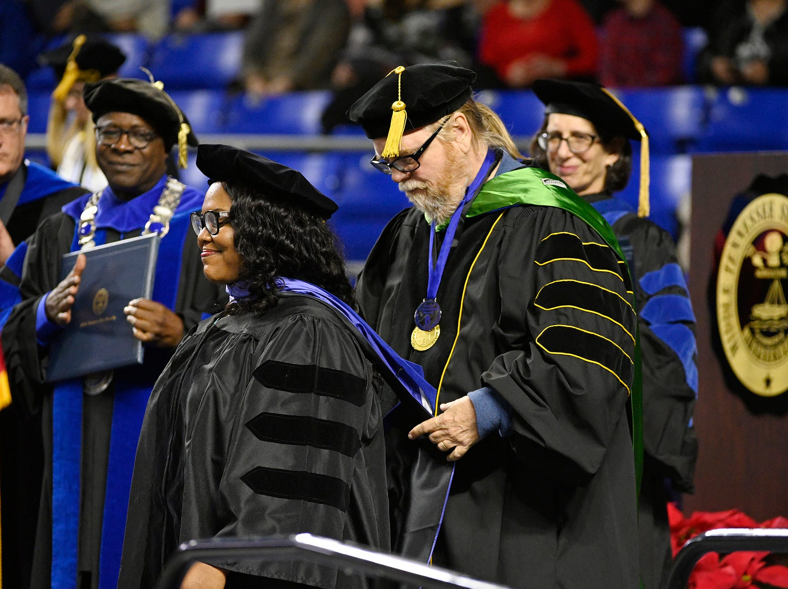 Marquita R. Reed, center, smiles with pride as Carroll Van West, head of MTSU's Center for Historic Preservation and a lead professor in the Public History Program, helps her don her doctoral hood  Saturday, Dec. 15, at the university's fall 2018 morning commencement ceremony in Murphy Center. Looking on are, from left, University Provost Mark Byrnes, MTSU President Sidney A. McPhee and Cheryl B. Torsney, vice provost for faculty affairs. Reed, who is collections manager at the National Museum of African American Music in Nashville, was one of 260 graduate students and 1,471 undergraduates receiving their degrees in Saturday's dual ceremonies.