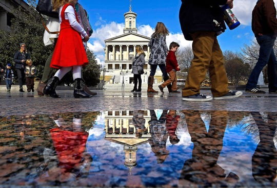 Visitors are reflected in a pool of water from recent rains as they walk across Legislative Plaza with the Tennessee state Capitol in the background on Jan. 9, 2018.