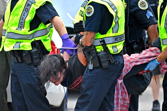 Jeannie Alexander is carried off after being arrested with other protesters blocking the entrances of Nashville-based CoreCivic, the nation's largest owner and operator of private prisons, Monday, Aug. 6, 2018, in Nashville, Tenn.