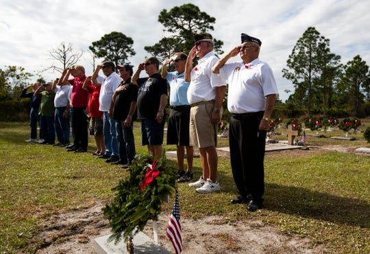 Members of Golden Gate Veterans of Foreign Wars Post 772 salute to pay homage to the 94 veteran gravesites that were restored and decorated by wreaths during a Wreaths Across America ceremony Saturday, Dec. 15, 2018, at Lake Trafford Memorial Gardens in Immokalee.