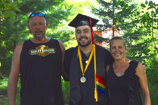 Andrew Atkins stands with his stepdad Heath, left, and his mom, Gerri.