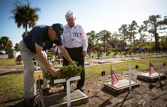 Members of Golden Gate Veterans of Foreign Wars Post 7721, along with other guests, gathered Saturday, Dec. 15, 2018, to place Christmas wreaths at the 94 restored veterans gravesites at Lake Trafford Memorial Gardens in Immokalee. The ceremony took place as a part of a larger tribute to veterans called Wreaths Across America. Ed Messer, left, a Vietnam War veteran, helps Wayne Murphy, right, a Navy veteran, place a wreath on one of the graves.