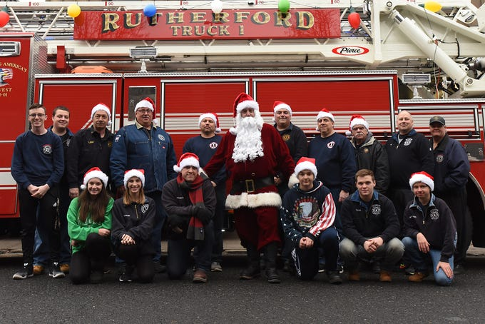 The Rutherford Fire Department escorts Santa around Rutherford on Saturday December 15, 2018. The Rutherford Fire Department poses for a photo with Santa in front of one of the trucks.