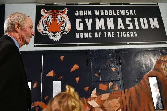 Palisades Park High School holds a ceremony to name the gym after John Wroblewski, long time athletic director on Friday December 14, 2018. John Wroblewski stands in front of the newly unveiled sign in the hallway outside the gym.