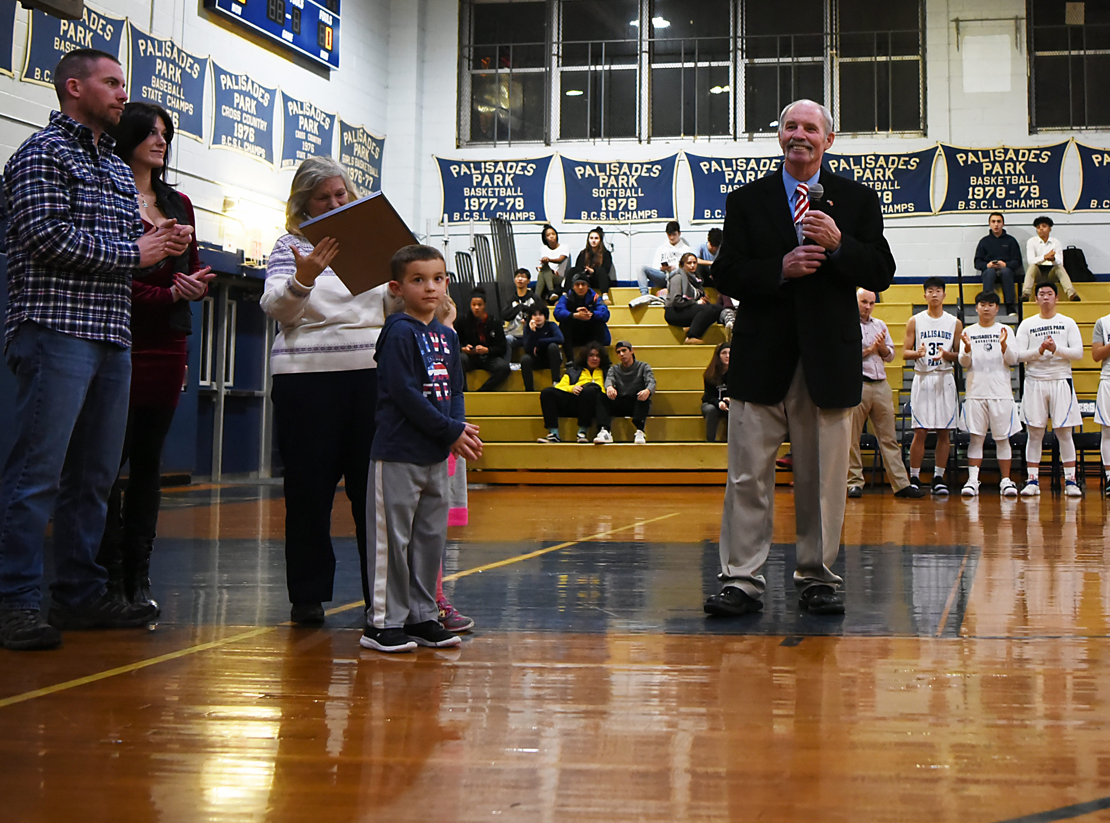Palisades Park High School holds a ceremony to name the gym after John Wroblewski, long time athletic director on Friday December 14, 2018. John Wroblewski says a few words on the court as his family and the boys basketball team cheers him on.