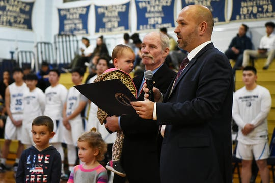 Palisades Park High School holds a ceremony to name the gym after John Wroblewski, long time athletic director on Friday December 14, 2018. John Wroblewski and his grandchildren stand on the court as Superintendent Dr. Joseph Cirillo says a few words.