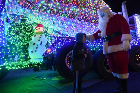 Salomone Brothers Inc. concrete trucks decorated in lights appears at Sip n Swirl in Little Falls on Saturday December 15, 2018. Carson Welhorsky, two years old, sits on his grandfather, Mark Welhorsky's shoulders, as they look at the brightly lit truck.