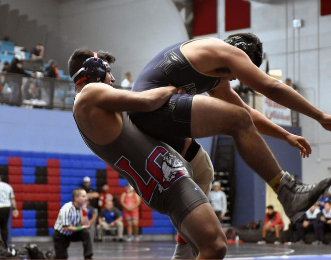 Las Cruces High's Austin Salas lifts his opponent off the mat for a take down as he won his match 8-6 for the right to wrestle for third place at this year's Las Cruces Wrestling Invitational.