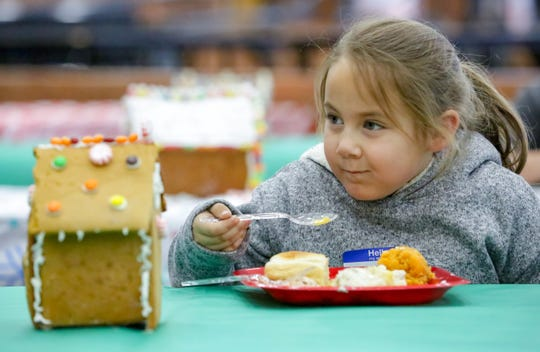 Cali Houston, 6, of Las Cruces, enjoys a holiday meal on Saturday, December 15, 2018 as Oñate High School hosts families from the Community of Hope at the school. Toys, clothing and food was given during the event.