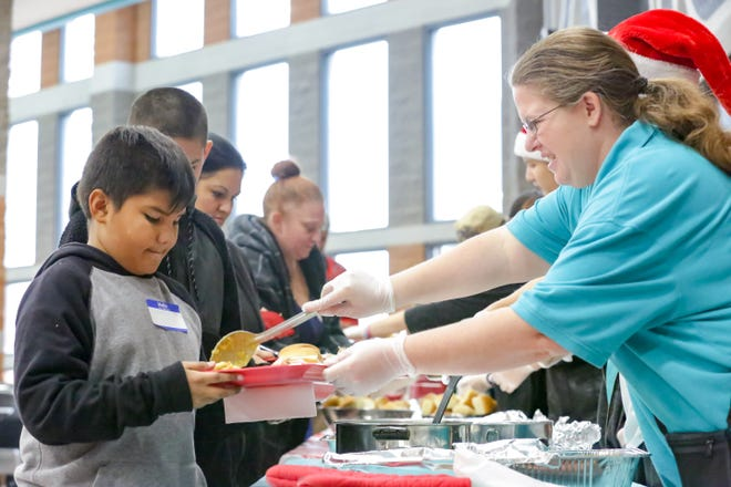 Robert Torres, 9, of Las Cruces, is served a portion of his holiday meal by Michele Gray, Oñate's sign language interpreter, on Saturday, December 15, 2018 as OHS hosts families from the Community of Hope at the school. Toys, clothing and food was given during the event.