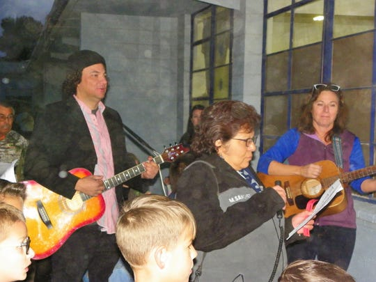 Mike Montoya, from left, Mary Sanchez and Krista Wierzbanowski lead Las Posadas at the St. Frances Cabrini Catholic School.