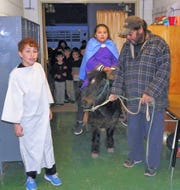 """Malachi Sanchez, from left, as Joseph, Frida Ortiz as Mary riding Bam Bam who is being lead by his owner Robert Sanchez at the St. Frances Cabrini Catholic School posadas. The posadas ended inside the school where the final """"inn"""" accepted the Holy Family."""