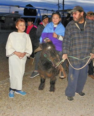 Malachi Sanchez, from left, as Joseph, Frida Ortiz as Mary riding Bam Bam who is being lead by his owner Robert Sanchez at the St. Frances Cabrini Catholic School posadas.