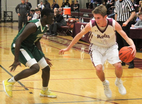 Seaholm's senior forward Alec Tripp (21) makes a move around Groves defender Roger Motley (11) in Friday's intra-city rivalry game.