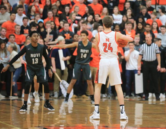 Novi's Alando Williams (13) and Jett Porter (14) wait to see what Northville's Steven Morrissey (24) will do with the basketball late in Friday's KLAA West Division game.