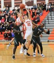 Northville's Daniel McLaughlin (22) tries to split Novi defenders Troy Aikins (2) and Jiovanni MIles (1) en route to the basket.