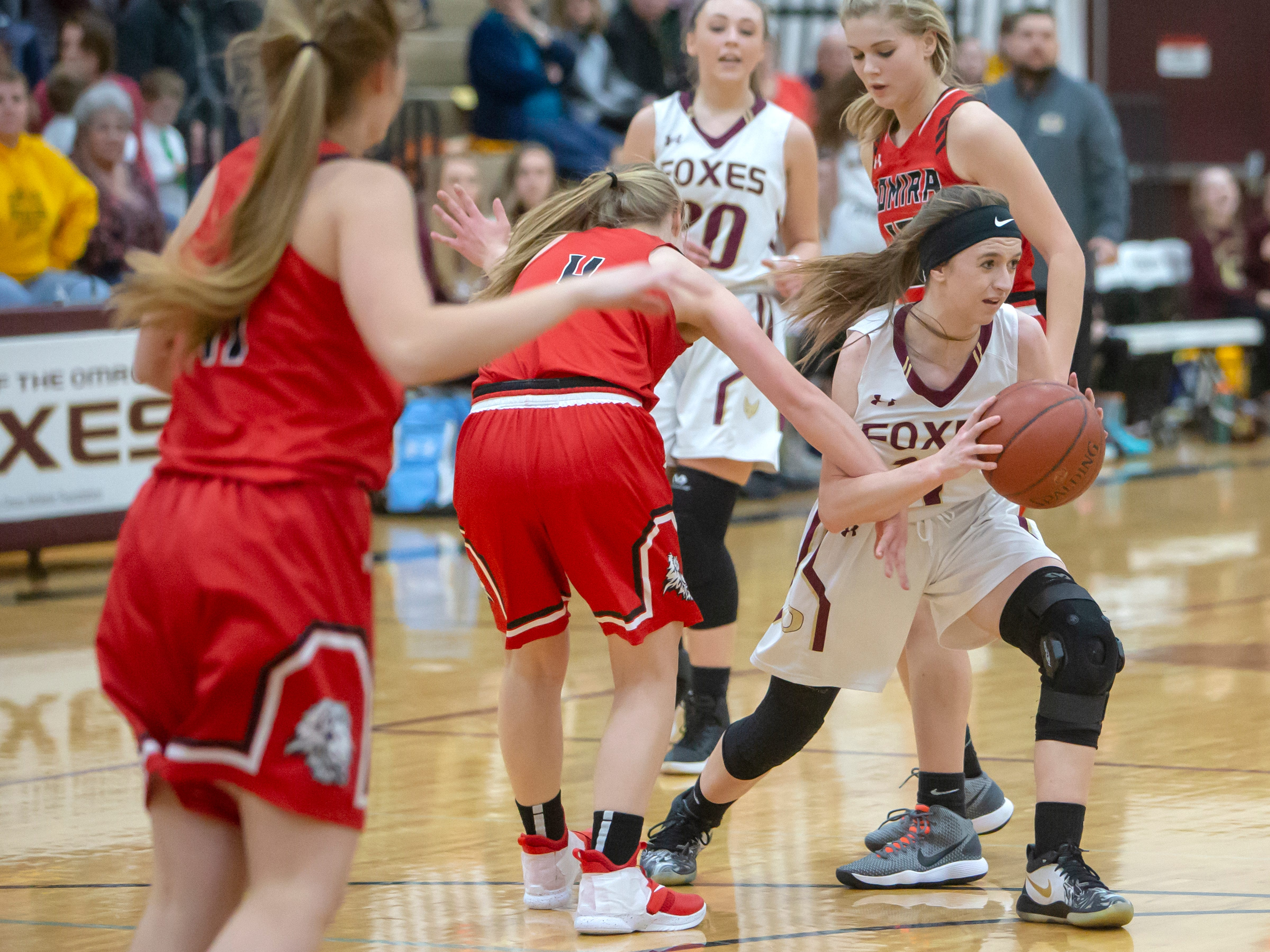Lomira's Lizzy Wulff hooks an arm around Omro's Danycka Milis moving the ball at Omro High School on Friday, December 14, 2018.
