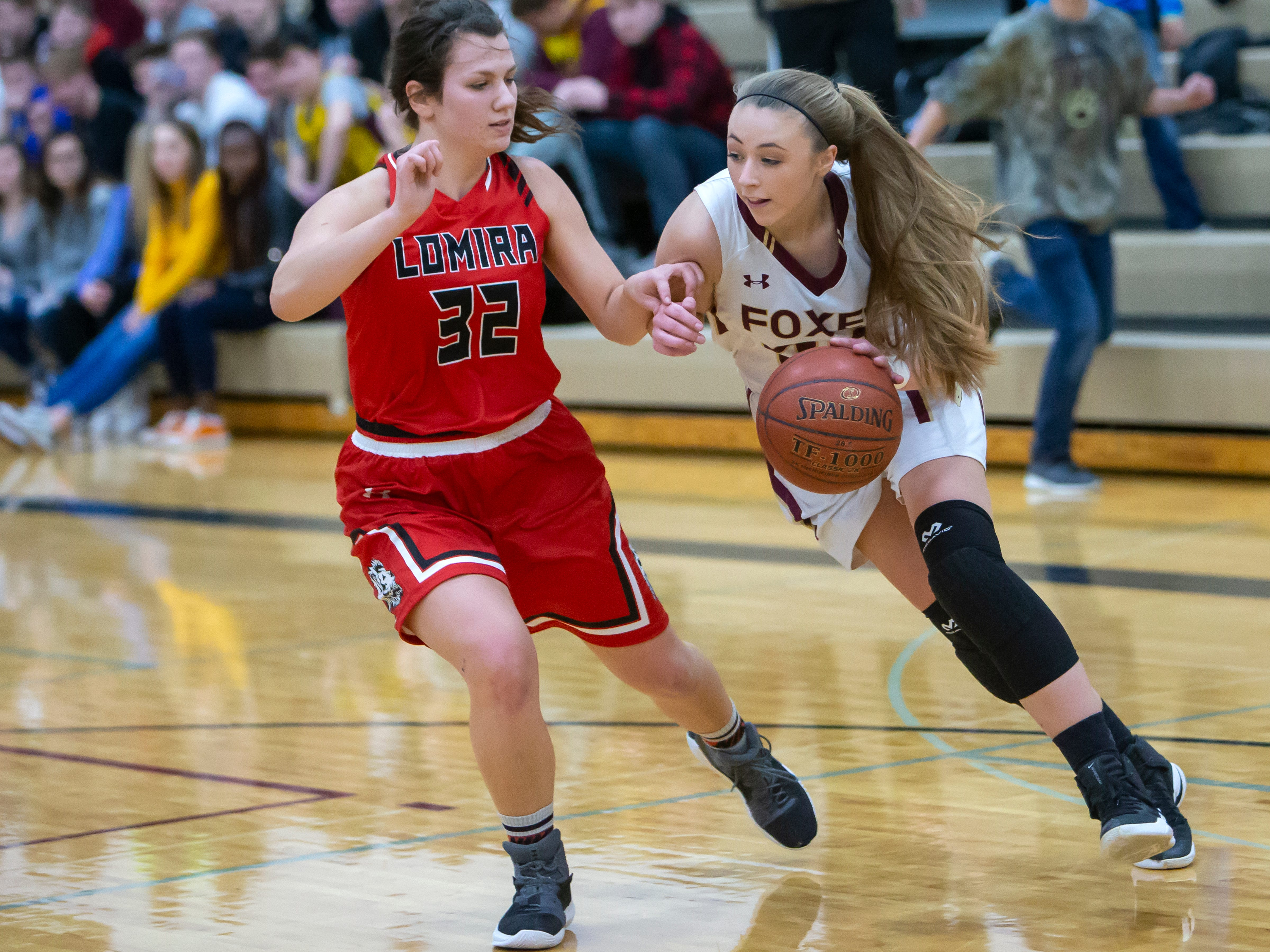 Omro's Taylor Lewis drives the ball to the basket around Lomira's Crystal Geiger at Omro High School on Friday, December 14, 2018.