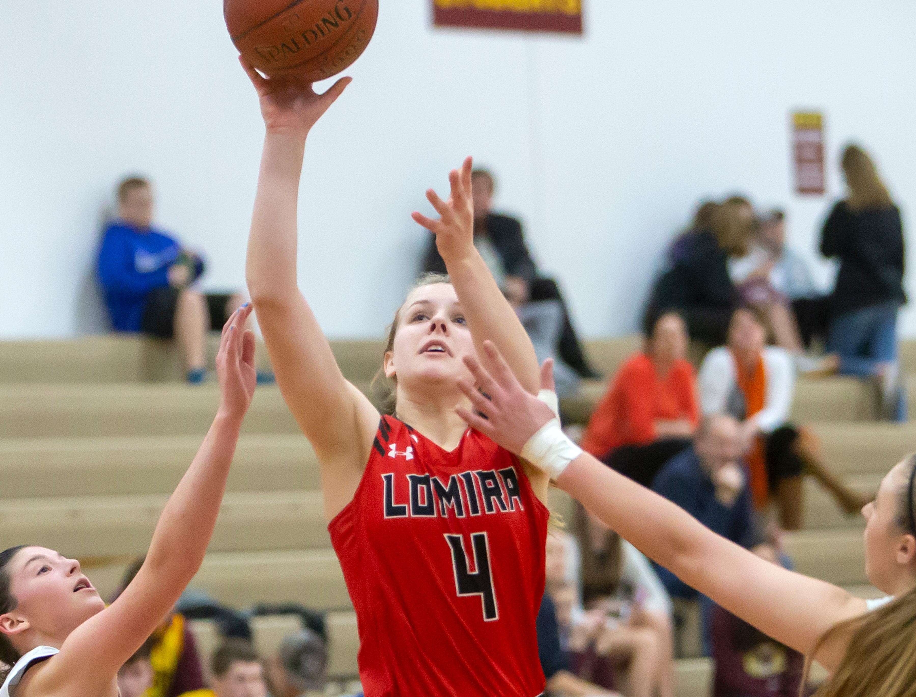 Lomira's Lizzy Wulff puts up a shot between Omro players at Omro High School on Friday, December 14, 2018.