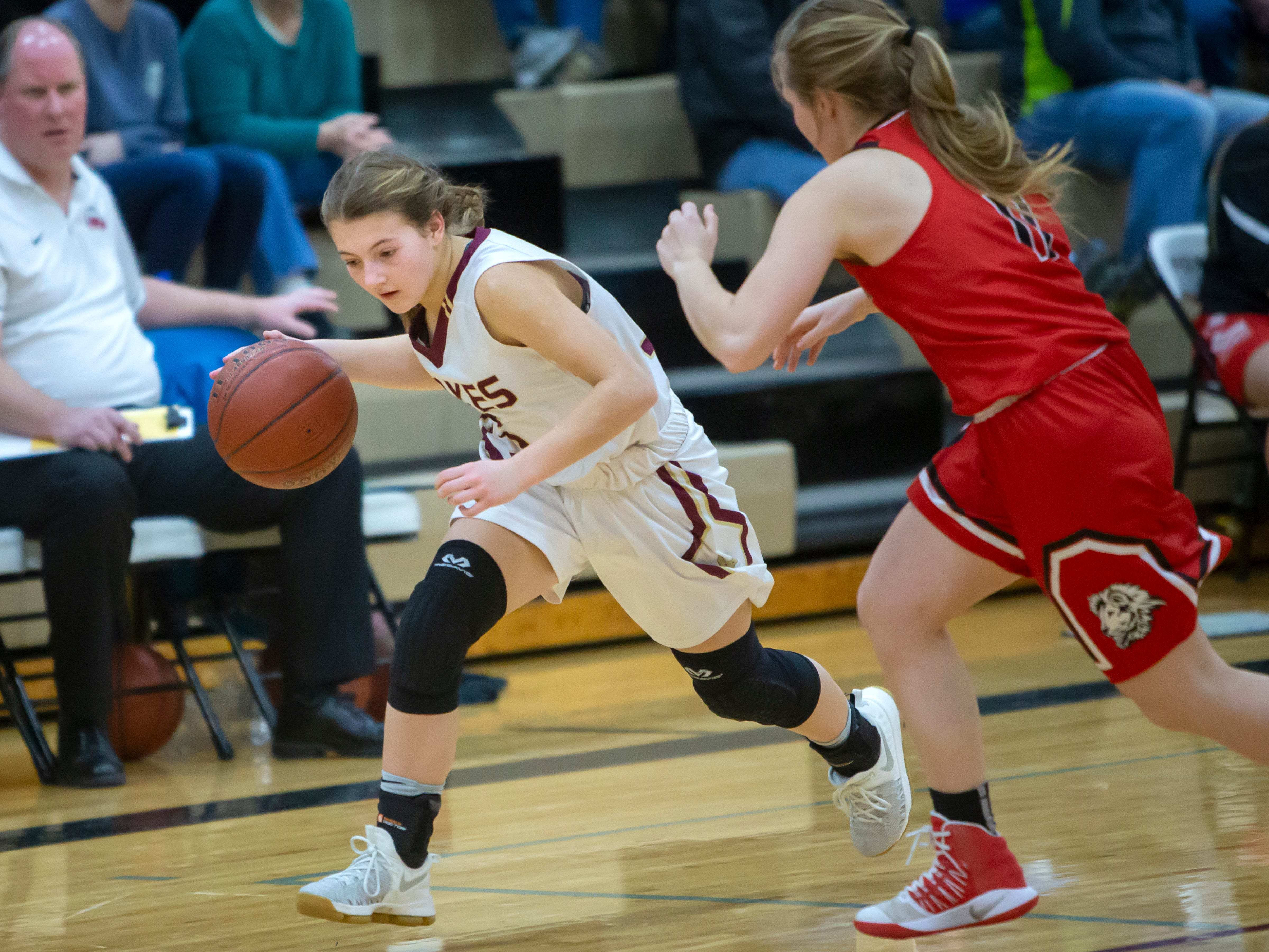 Omro's Hannah Fedderly runs the ball past Lomira's Samantha Doyle at Omro High School on Friday, December 14, 2018.