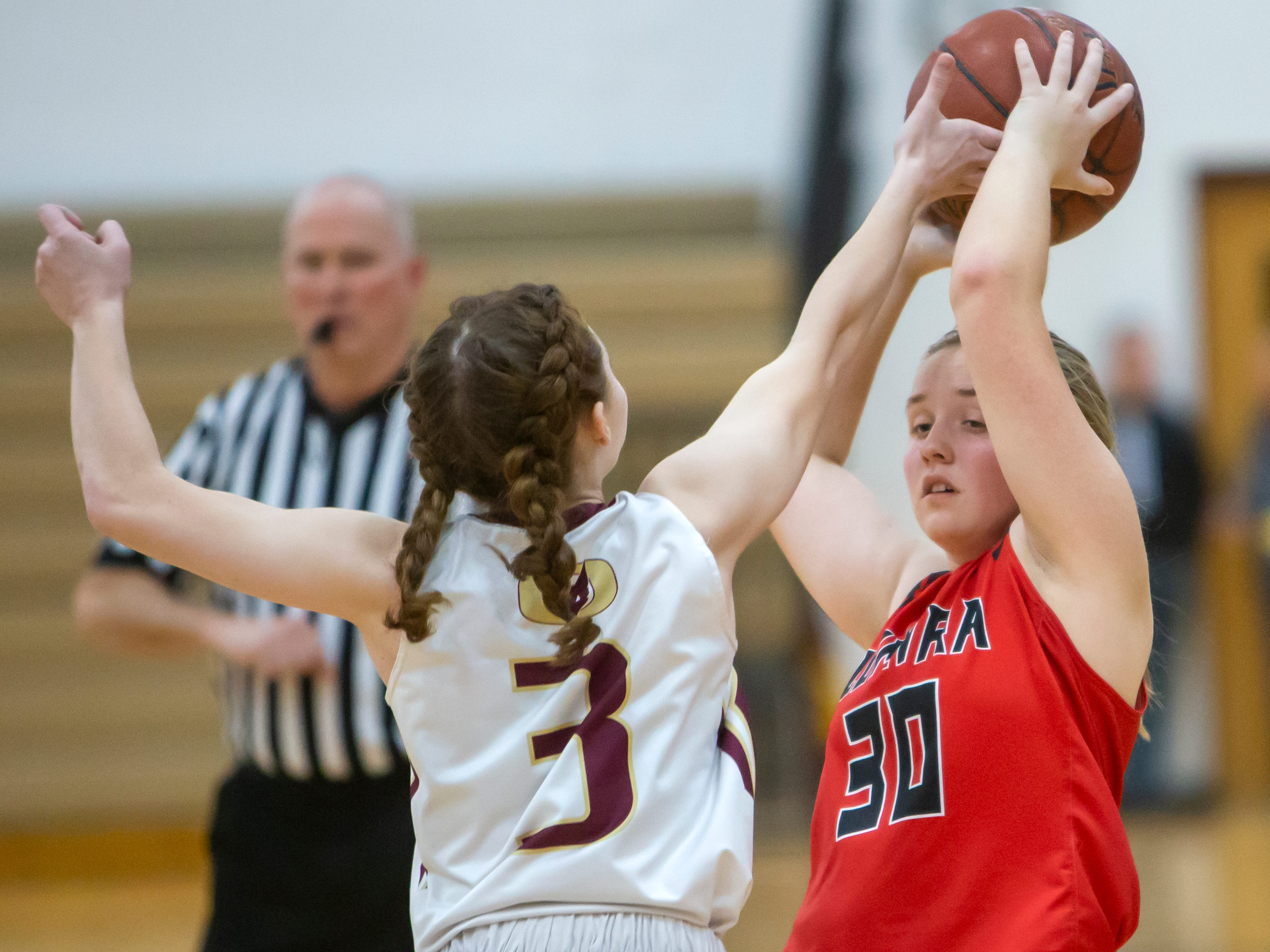 Omro's Brooke Beriau attempts to break the ball away from Lomira's Erin Ries at Omro High School on Friday, December 14, 2018.